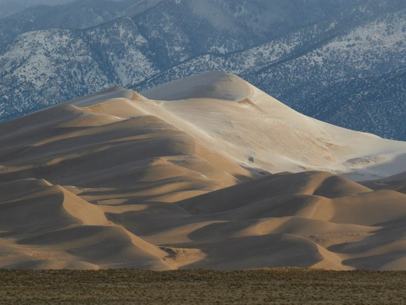 layers of beautiful sand dunes stacking against each other in the early morning light in colorado