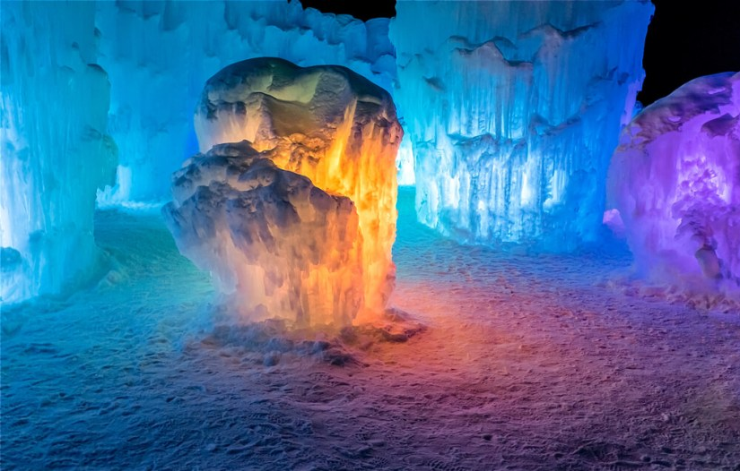 One room of the Dillon ice castle with blue, orange, and purple lighting creating a unique ambiance
