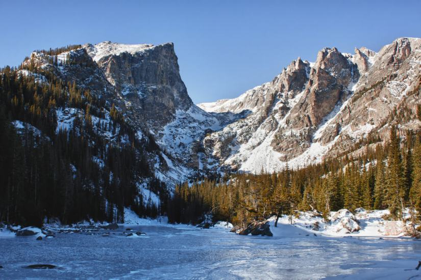 Emerald lake in rocky mountains national park, CO in winter with frozen ice sheet on the lake and snow