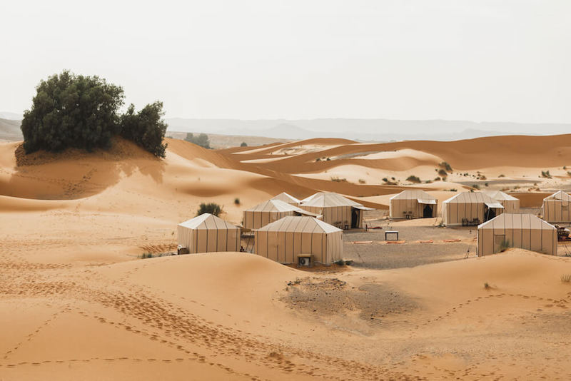 Eco tents in a glampsite in Morocco with views of the dunes and some desert shrubbery on a hazy day.