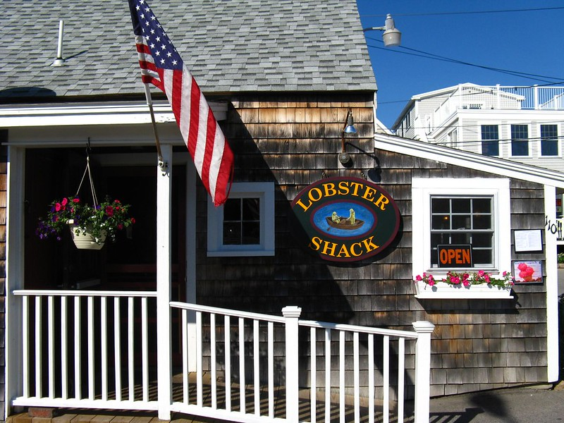 """Wood house with white trim and planter basks and american flag and sign that reads """"lobster shack"""" and """"open"""""""