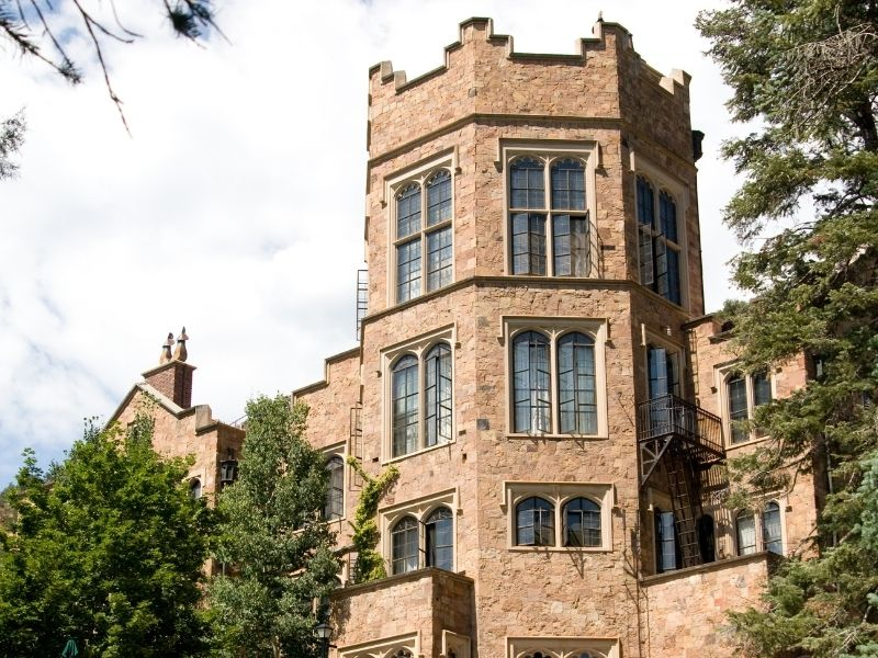 The historic castle of Glen Eyrie with tan brick and lots of windows and trees in Colorado Springs CO