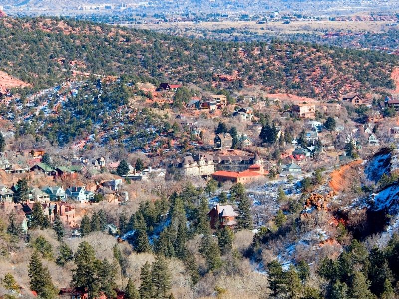 the reddish rock landscape of manitou springs in colorado dusted with a light layer of snow in the early winter time or late spring