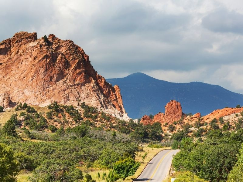 Road leading to Garden of the Gods park in Colorado Springs with green trees and red rocks