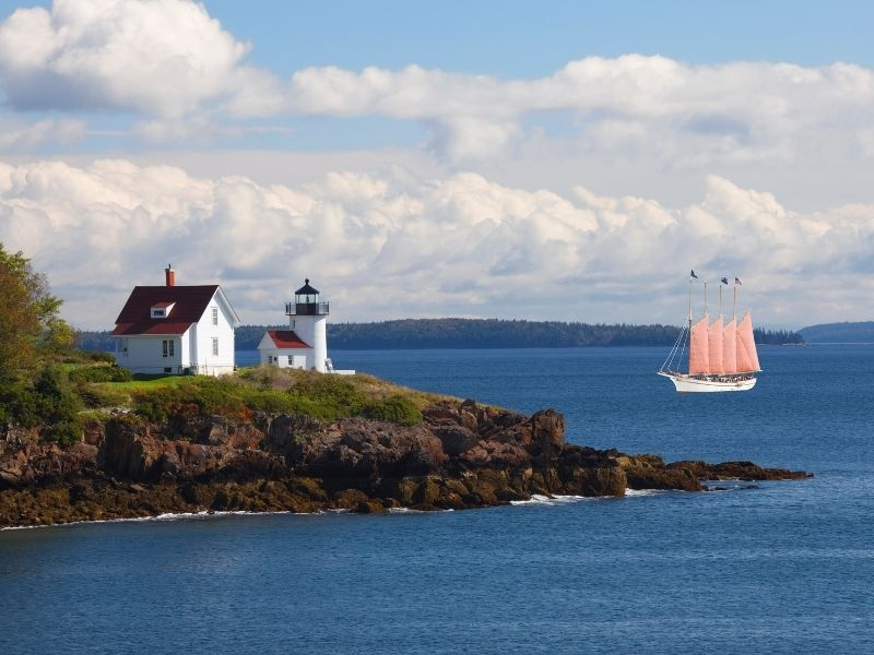 schooner boat with four peach-orange sails and the lighthouse on the island