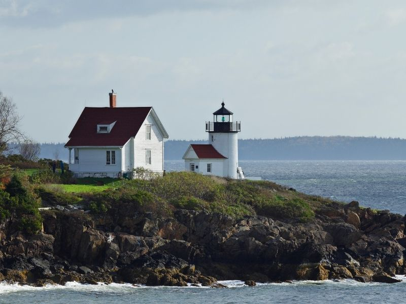 a beautiful white lighthouse with a red roof and lightkeeper house on a rocky outcropping in the bay near camden