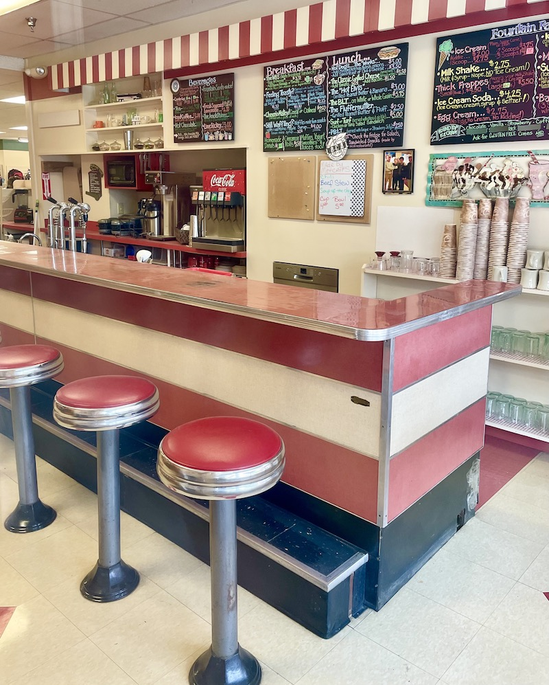 Bright red and white soda fountain selling ice cream, milk shakes, breakfast and lunch.