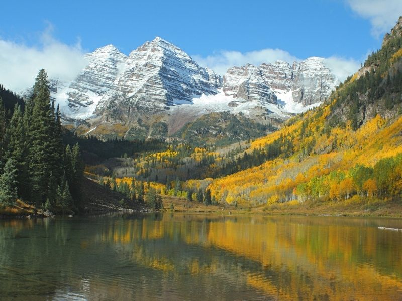 yellow aspens and evergreen trees reflecting in maroon lake like a painting with the snow-capped mountains behind it in autumn in colorado