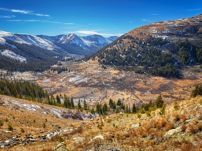 driving through the mountain pass of independence pass with road, yellow trees, light snow and mountains in the fall in colorado