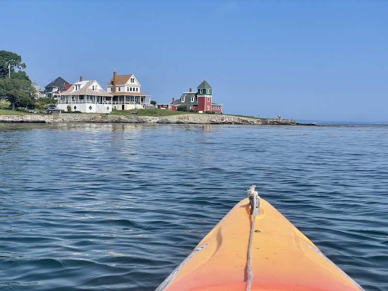 kayaking in an orange kayak pointing torwards orrs island houses after leaving bailey island