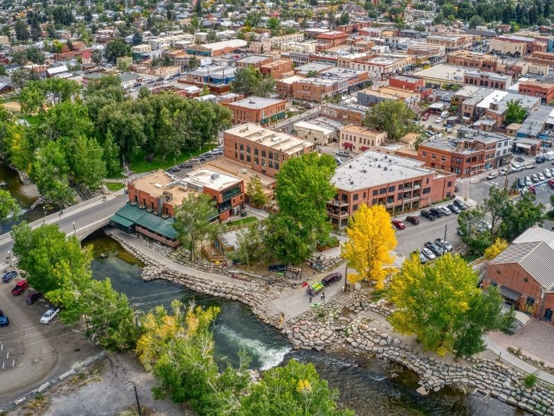 The Arkansas Whitewater Recreation Area and the red and orange buildings of downtown Salida in Colorado with yellow and green trees in early fall