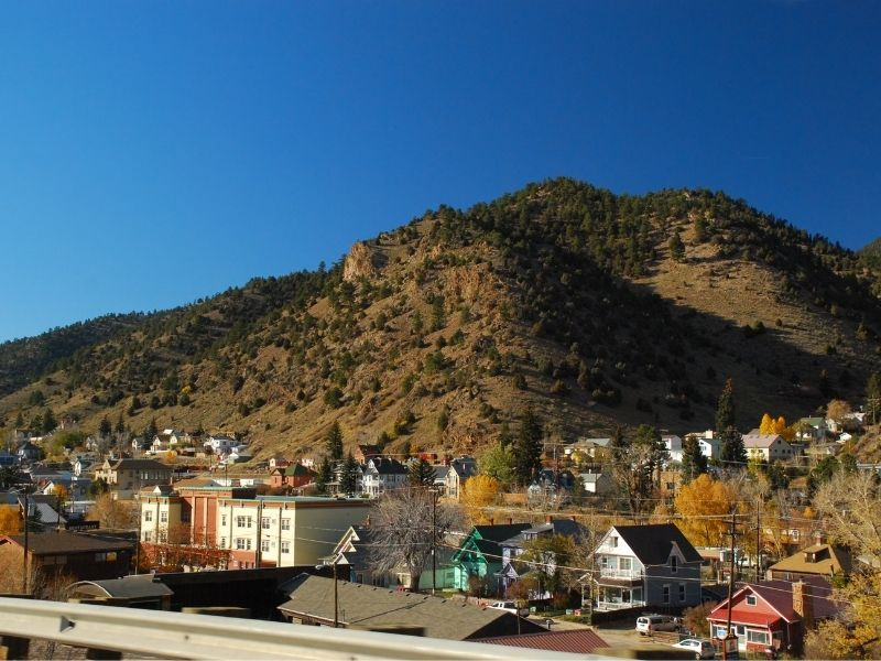 The charming mountain town of Idaho Springs Colorado with lots of old fashioned houses and a yellow-grass mountain with trees
