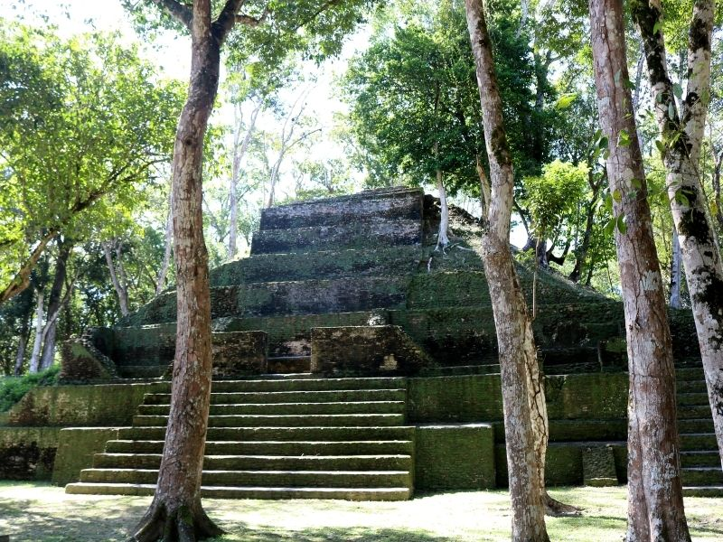 smaller pyramid at cahal pech ruins surrounded by trees and shaded