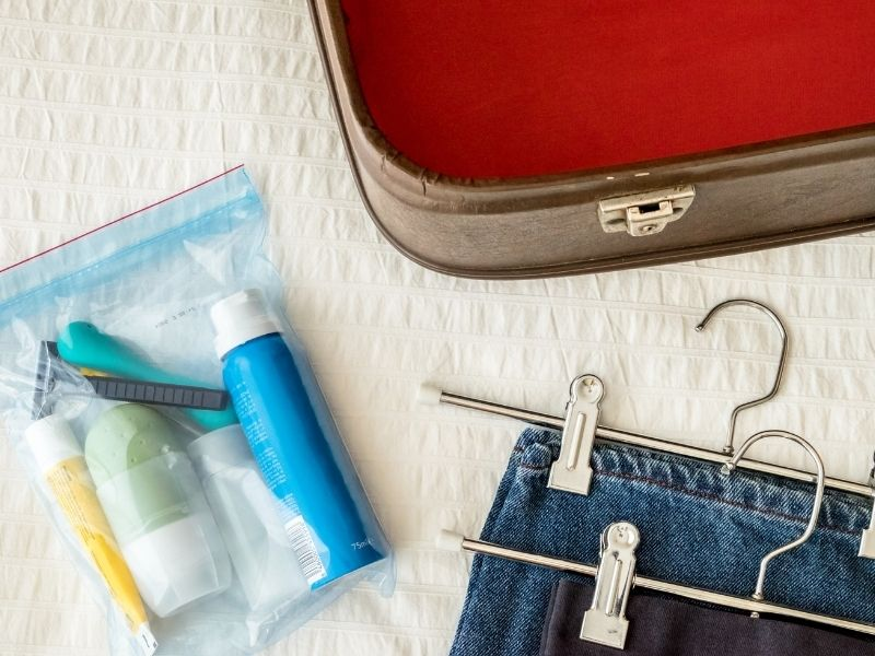 A toiletry bag and some pants and a luggage