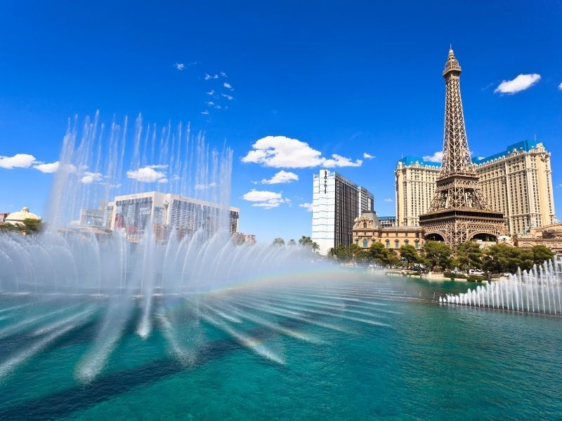 fountain in front of the bellagio during the day time making a small rainbow prism in the water with the eiffel tower visible in the background