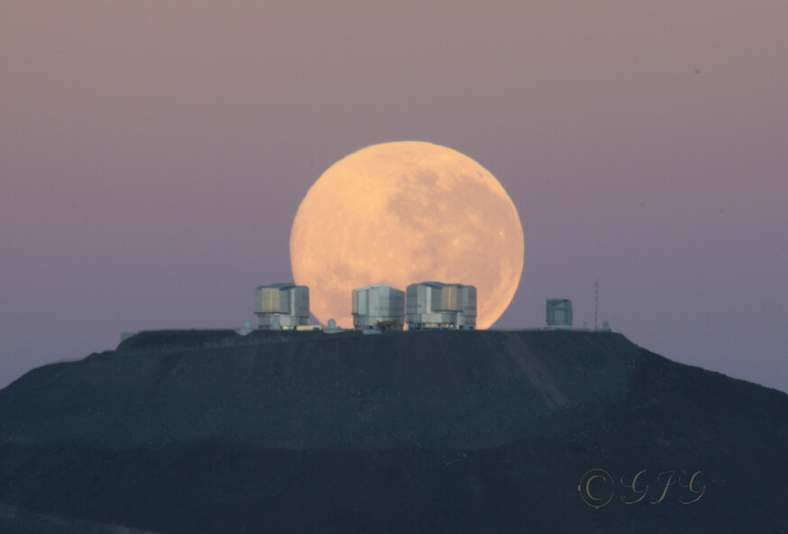"""Observatório Cerro Paranal do ESO. O monte Paranal, 2.635 metros de altura, no deserto do Atacama, Chile, é considerado um dos lugares mais secos da Terra. O ESO opera um conjunto de 4 grandes telecópios cada qual com um espelho principal com 8,2 metros de diâmetro. Esses telescópios podem operar em grupos de 2 a 3 formando um gigantesco """"interferômetro"""" que permite aos astrônomos observar detalhes como se estivessem usando um telescópio muito maior."""