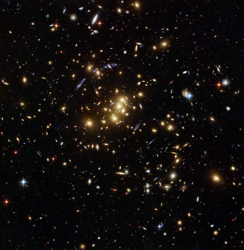 Este rico aglomerado galáctico, catalogado como CL 0024+17, permitiu aos astrônomos investigar a distribuição de matéria escura pelo espaço. As manchas azuis próximas ao centro da imagem são as visões distorcidas de galáxias muito distantes que não fazem parte do aglomerado CL0024+17. Estas galáxias distantes aparecem 'amassadas' por causa do desvio e da ampliação de sua luz realizada pela poderosa lente gravitacional do CL0024+17. Crédito: NASA, ESA, M.J. Jee and H. Ford (Johns Hopkins University)