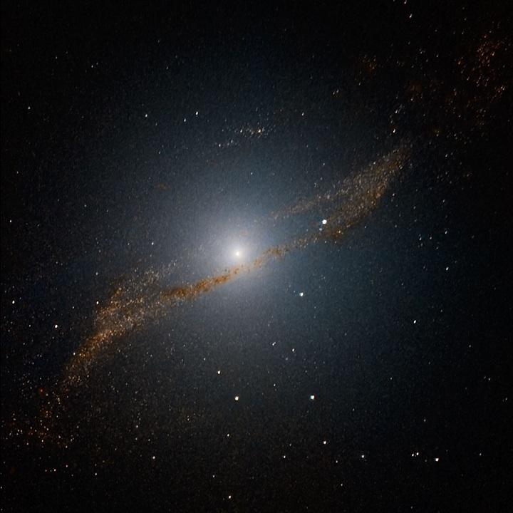 Esta imagem da região central da galáxia elíptica Centaurus A revela os restos em formato de paralelogramo de uma galáxia elíptica menor canibalizada pela galáxia gigante. Crédito: ESO/Y. Beletsky