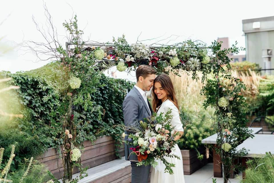 An ethical wedding photo shoot featuring the bride and groom in front of a earthy, floral arch which is a fresh tip for planning ethical weddings on a budget.