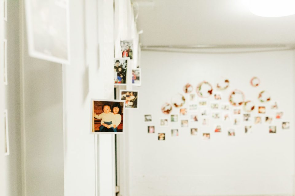 Photos hung up around a room against white walls