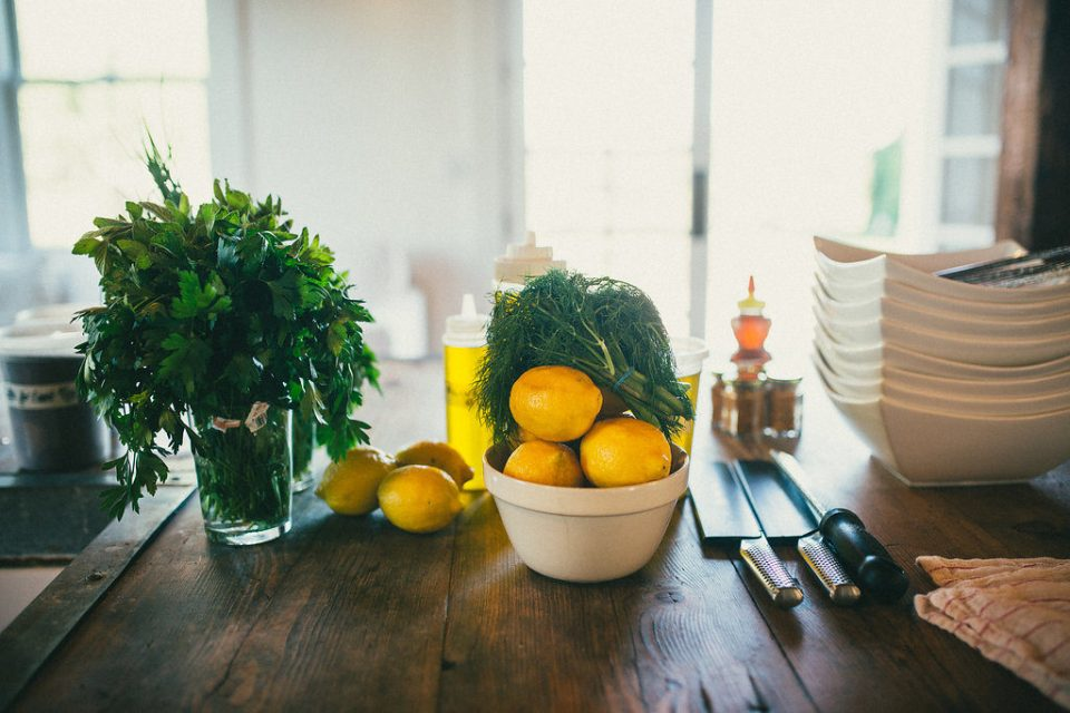 lemons, greens, and utensils laid out on wooden table