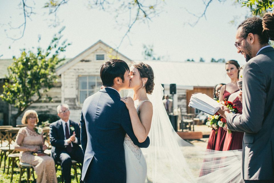 bride and groom kiss in front of family and friends