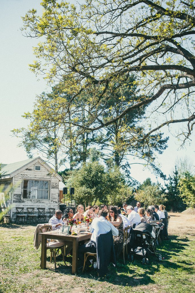 Guests sit outside at a table under the tree