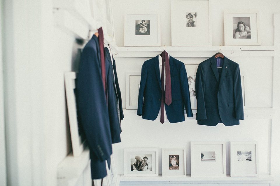 three of the suit jackets hung up on a white wall with photographs