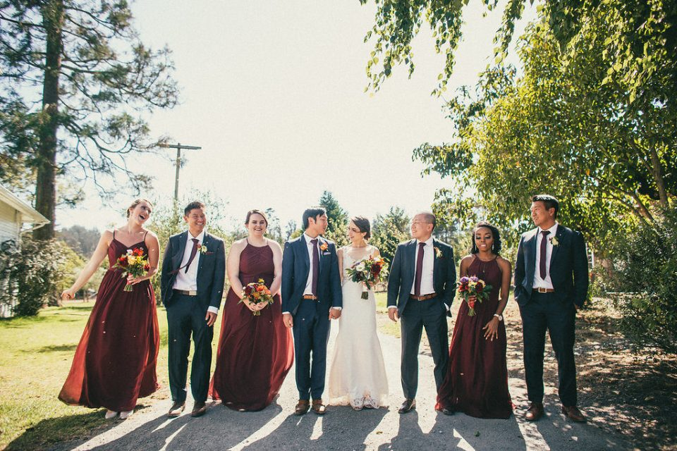 Bride and groom walk in the middle of their respective parties