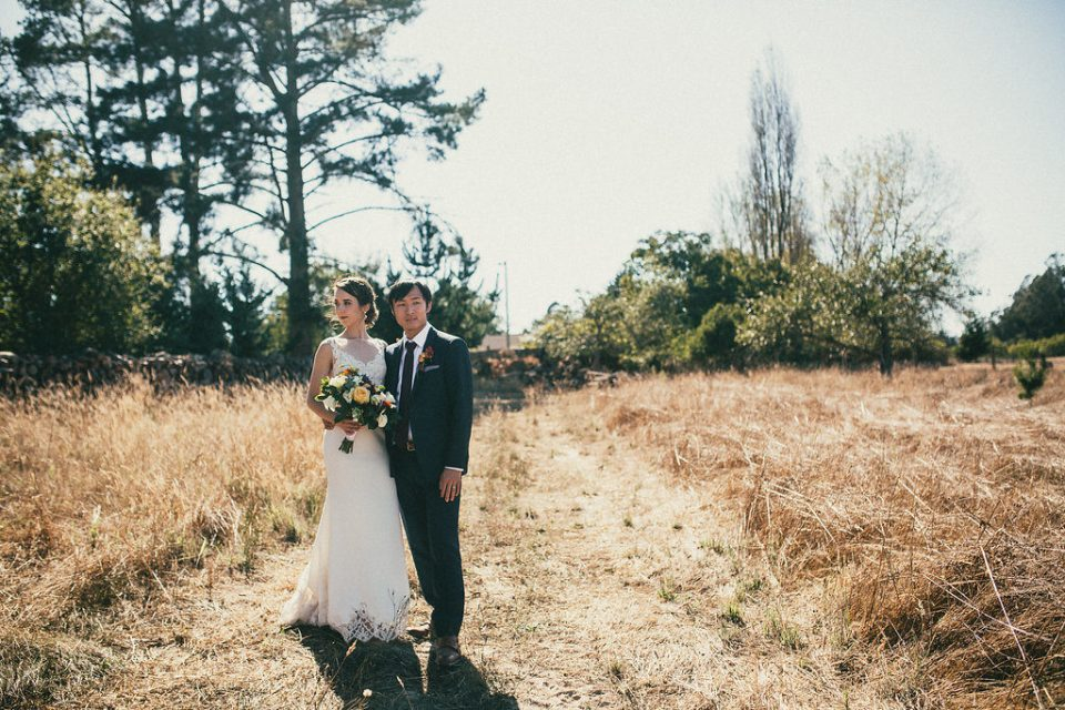Bride and groom stand side-by-side in a field