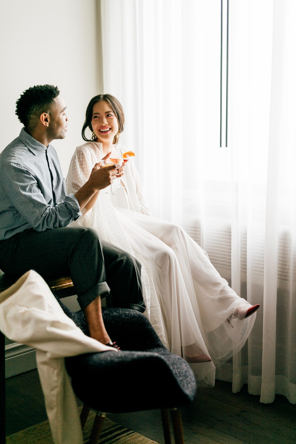 Ethically styled couple sits near window, clinking glasses