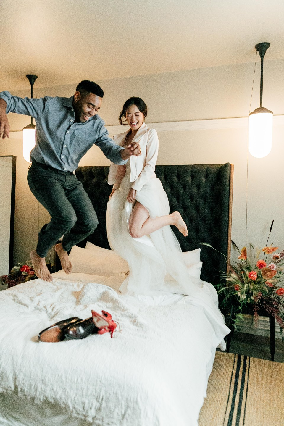 ethically dressed man and woman jump on hotel bed
