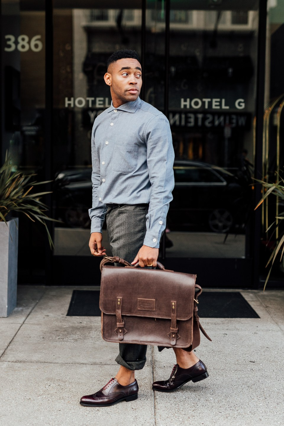 Ethically styled man walks on street, holding briefcase