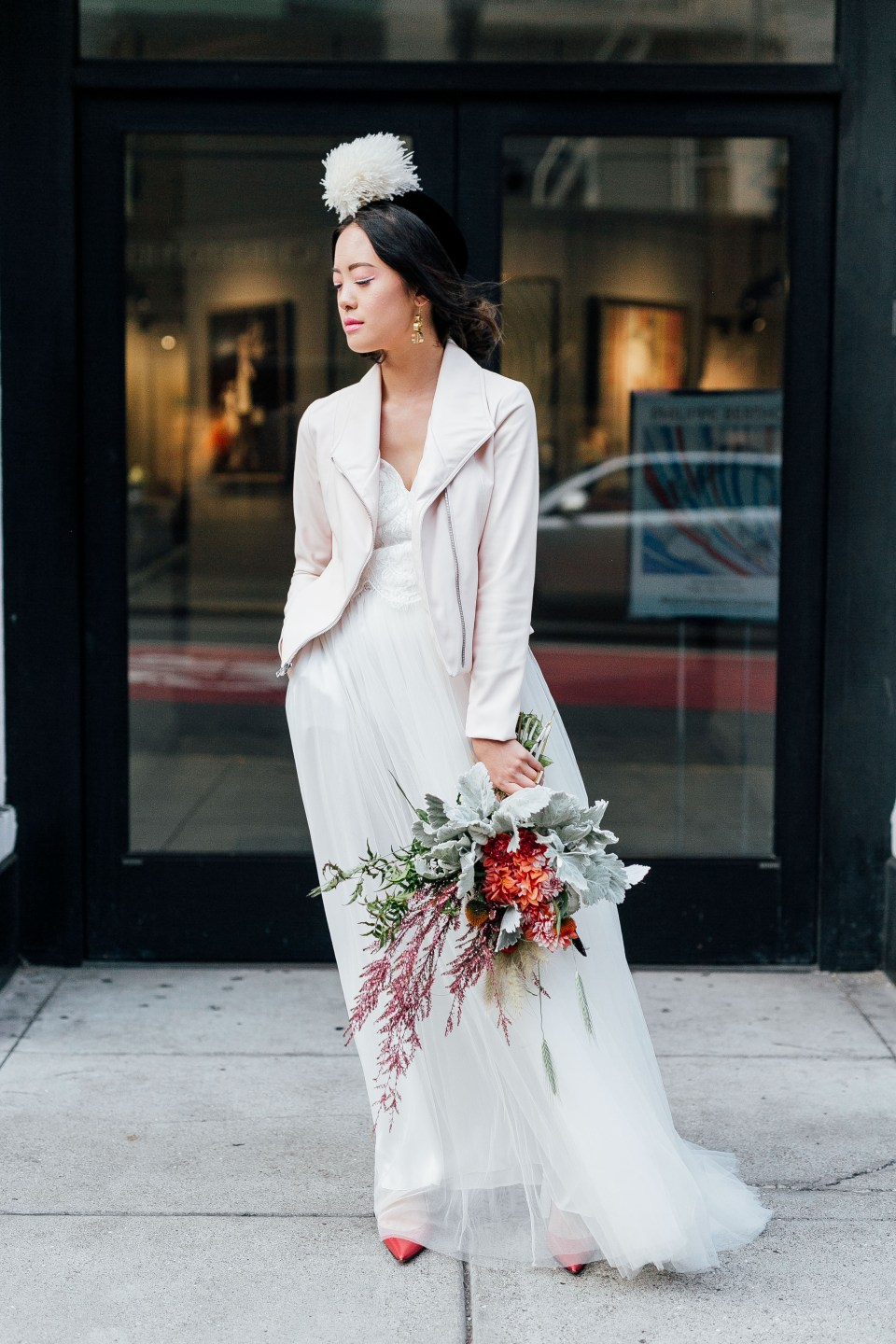 Ethically styled woman stands on street, holding bouquet