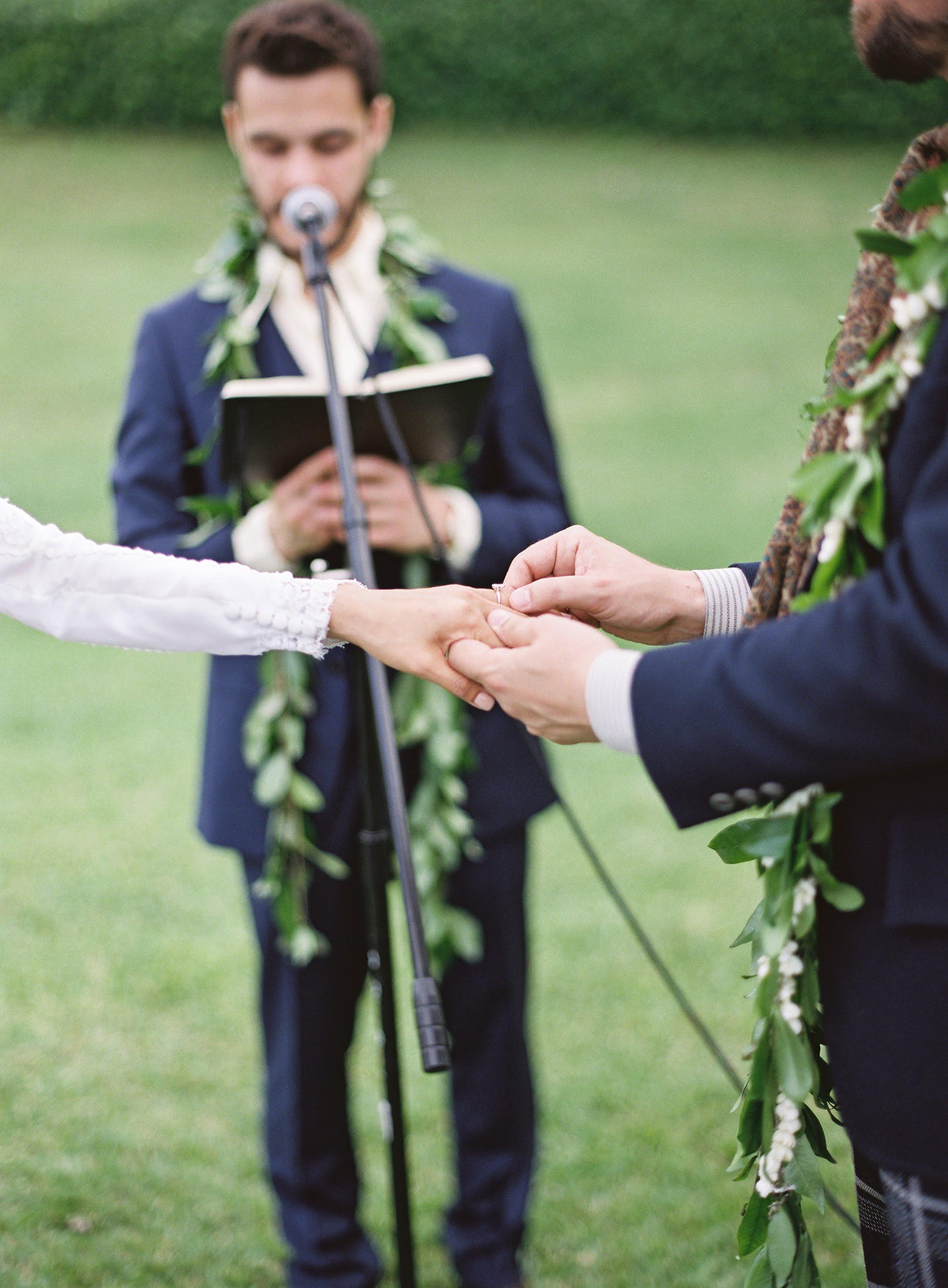 Groom slides ring onto bride's finger