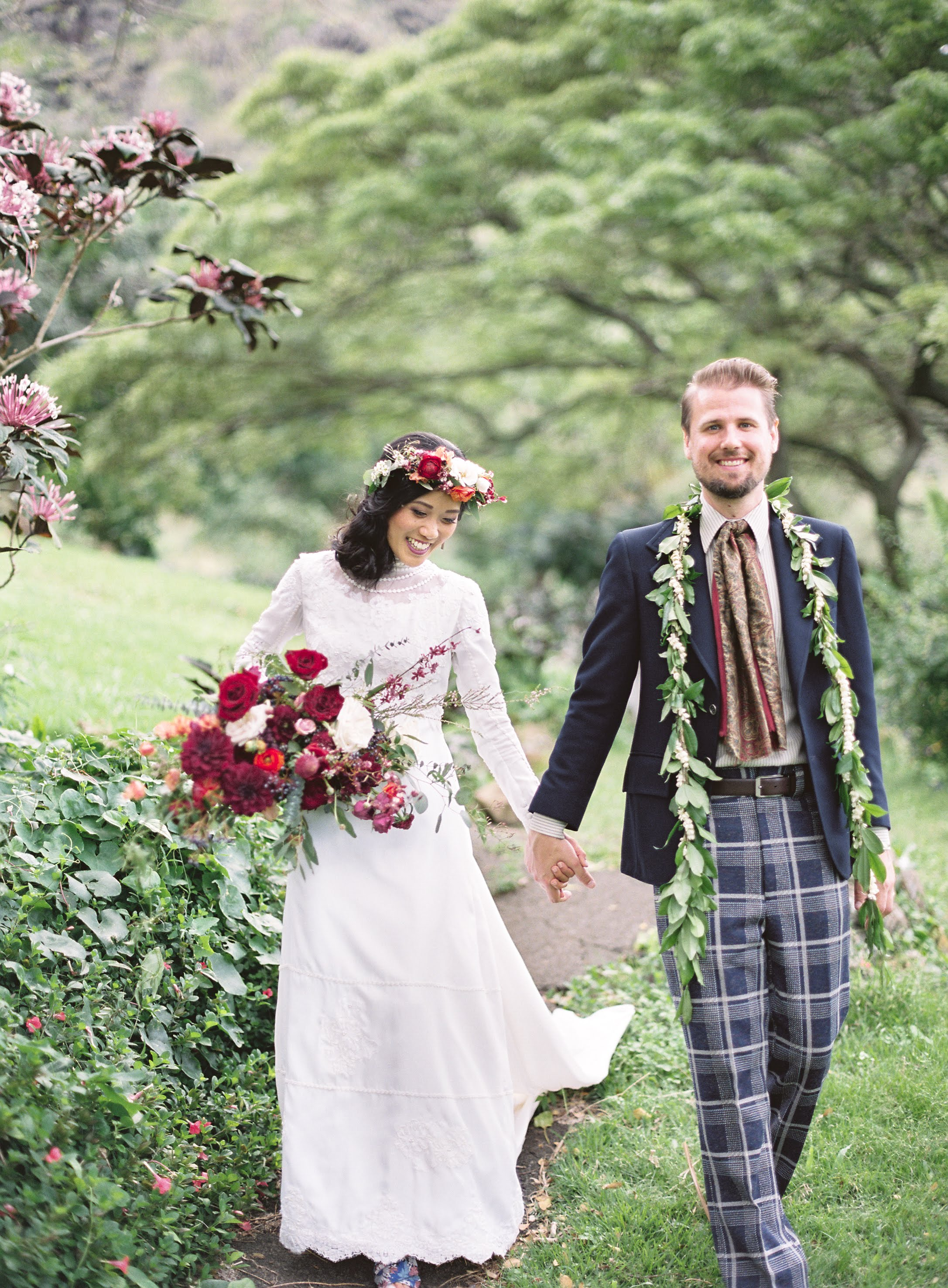 Bride and groom hold hands, walking through green foliage