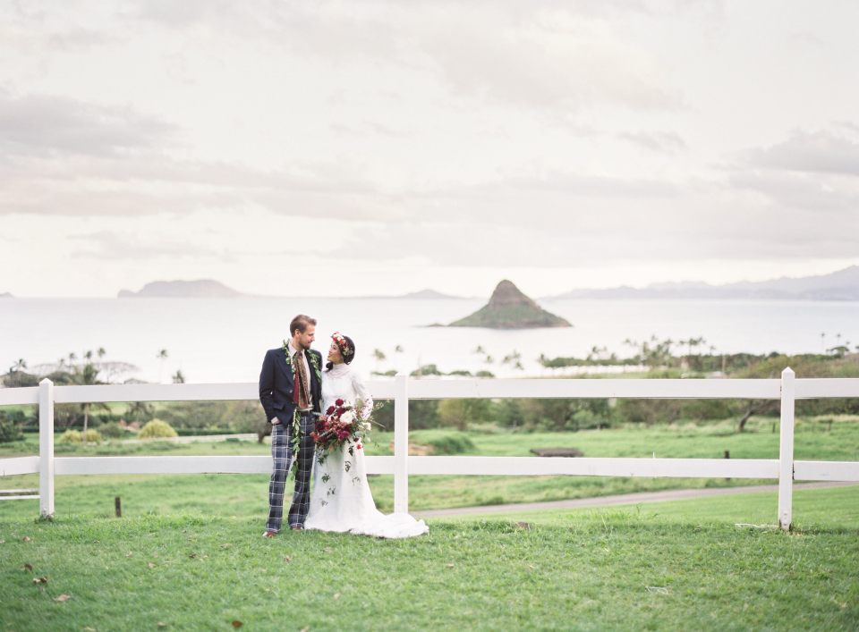 Bride and groom stand together, in front of beautiful beach