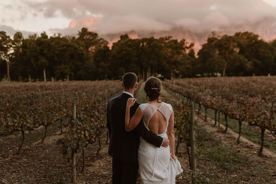 The bride and groom embrace and look out at the sprawling vineyards in Cape Town, South Africa where they had their socially conscious wedding.