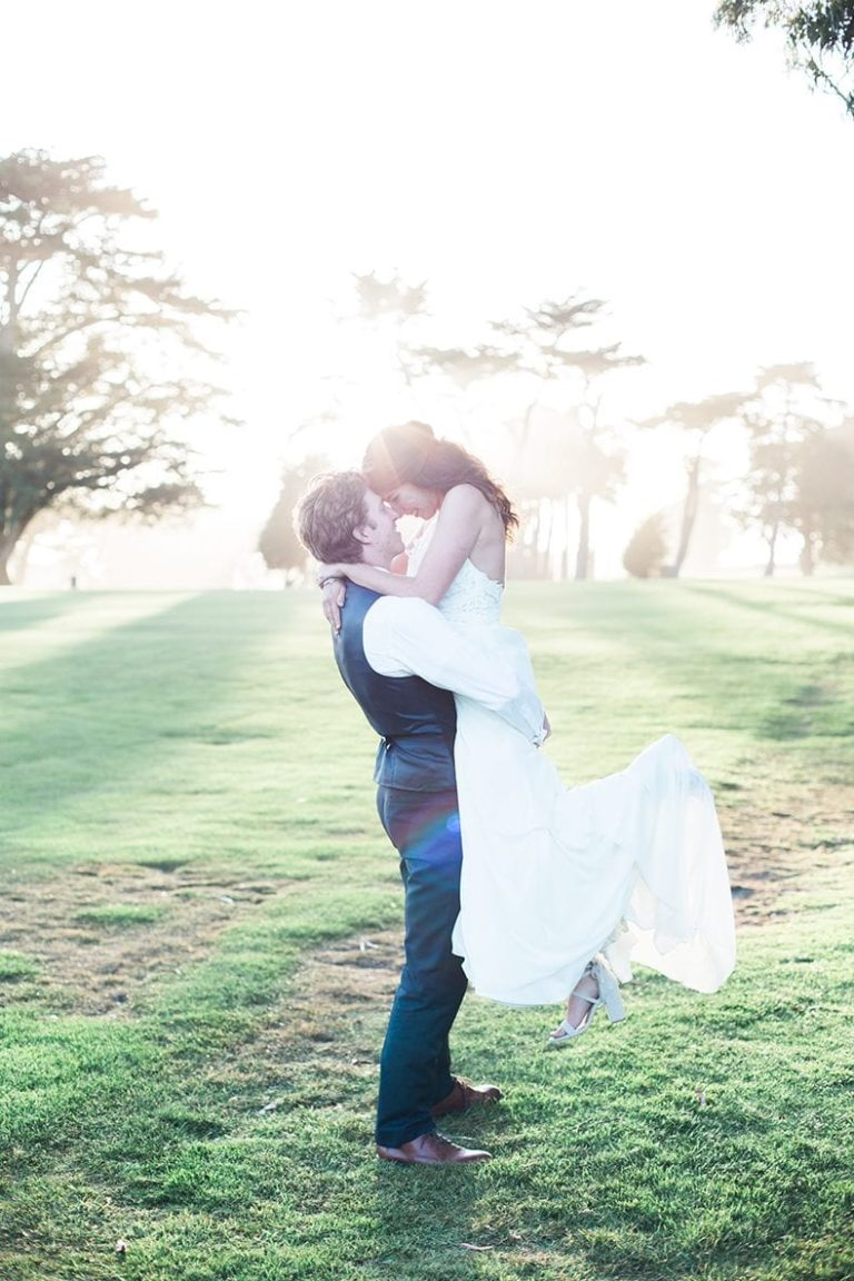 Davida and her husband hug in an open green field. Davida shares her secrets and truths about wedding planning.