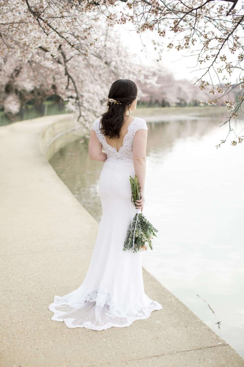 A bride poses wearing an open back eco friendly wedding dress from American brand, Krustallos Couture.
