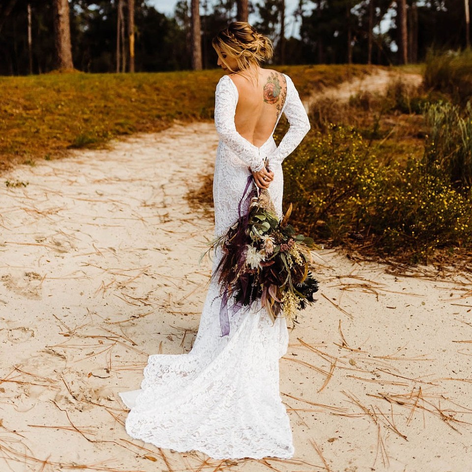 A bride wears an open back fair trade wedding dress
