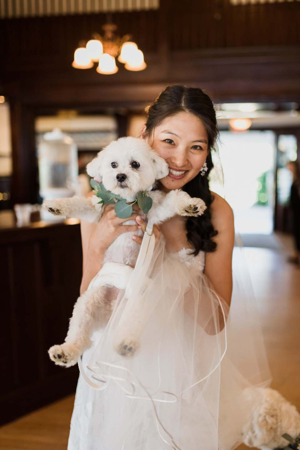 Bride Monica holds her dog on her wedding day.