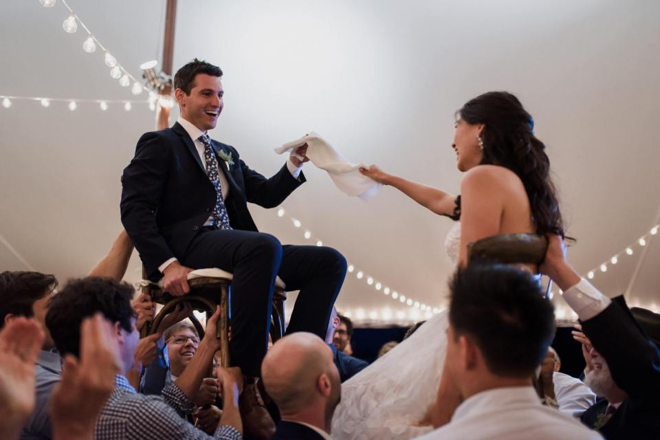 The bride and groom are lifted on chairs as Jewish tradition at their wedding.