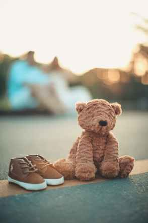 brown bear plush toy beside pair of toddler s brown and white shoes on ground in selective focus photography