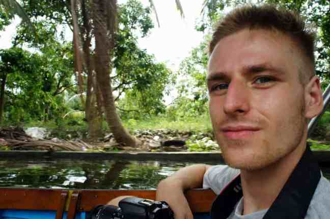 Cez holding a camera, siting in a boat