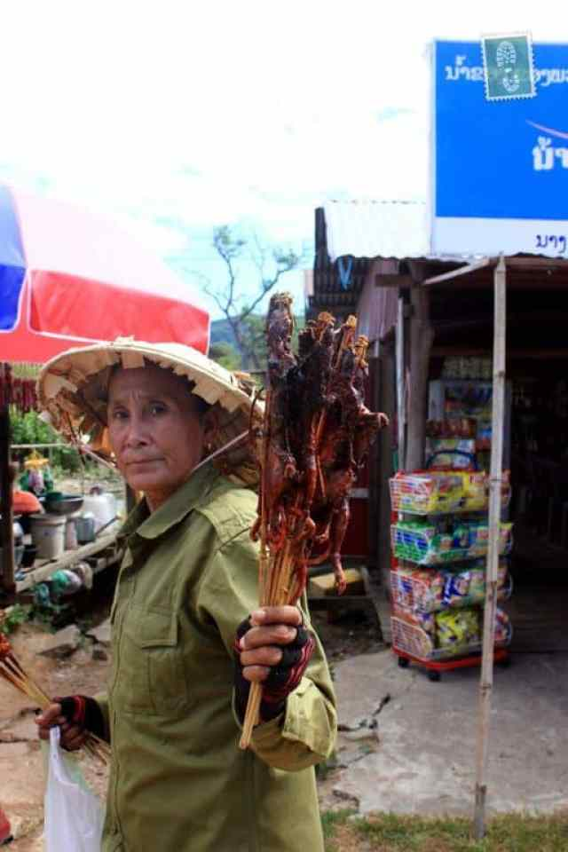 A lady selling grilled rats