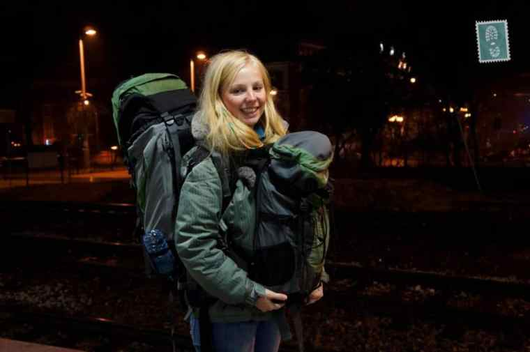 A girl carrying two backpacks one in front of her one on her back
