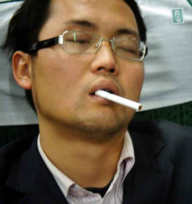 Chinese guy sleeping and holding a cigarette in his mouth