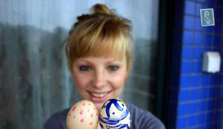 a girl is holding two easter eggs painted and she smiles