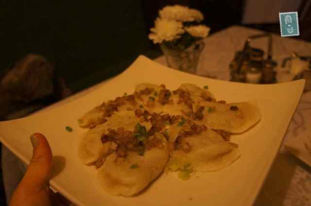 A plate of pierogi with fried onion and chives